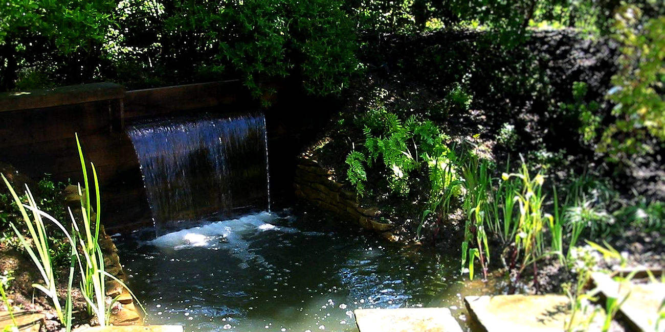 Large waterfall and stepping stones in a wildlife pond